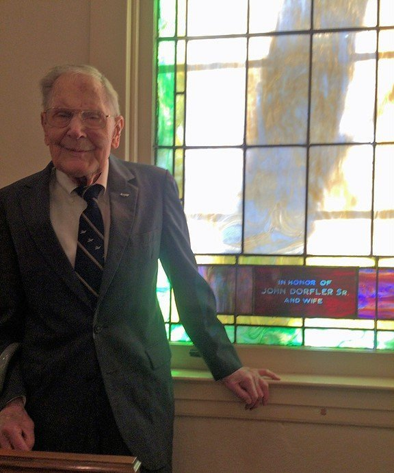 Roy Dorfler standing by the window in Idlewylde United Methodist Church that honors his parents. John Dorfler helped build the church, which opened in 1917.